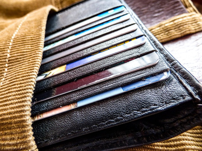 An open wallet, full of credit cards, sticking out of a pocket.
