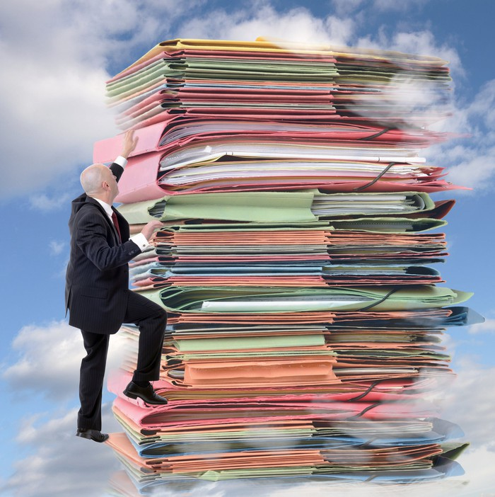 Man climbing a sky-high stack of paperwork