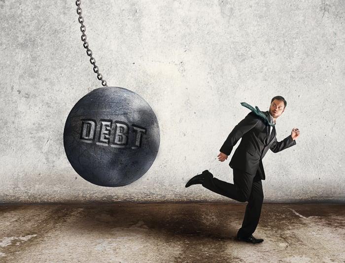 Debt ball swinging towards businessman