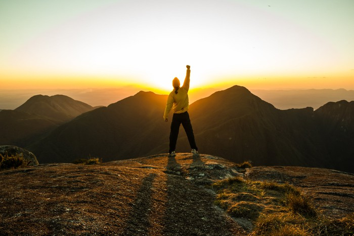 A man raising his hands in celebration, standing on a mountain top and overlooking a sunset.