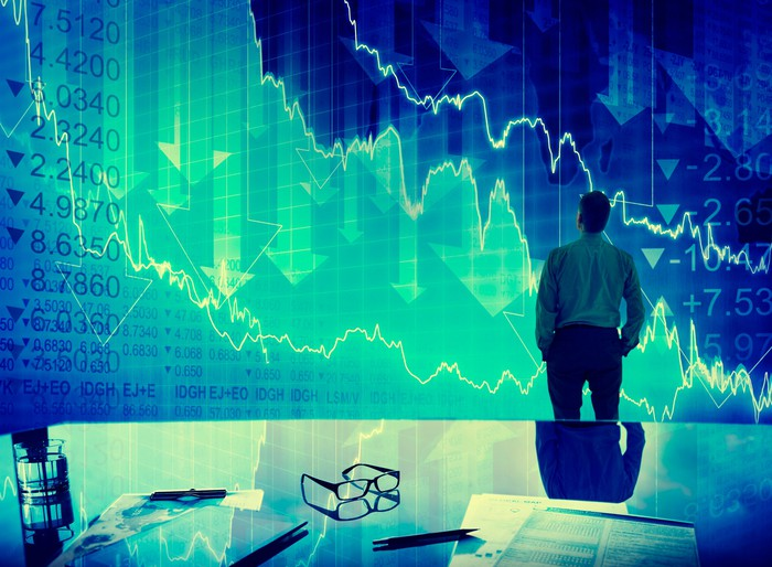 Businessman stands in front of a stock market chart with down arrows on it