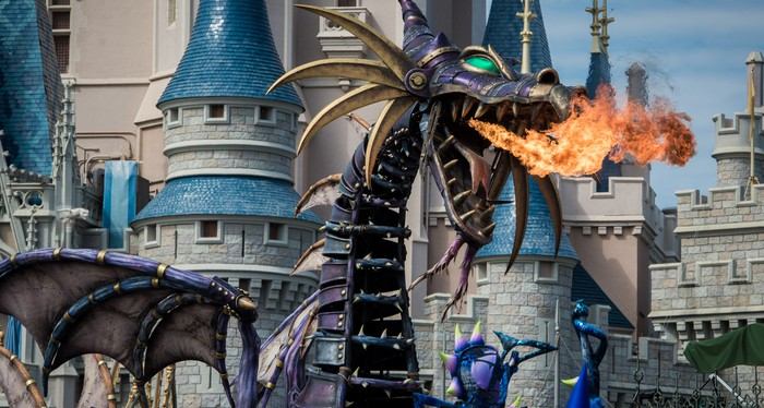 Dragon Maleficent breathing fire outside Cinderella's iconic castle.