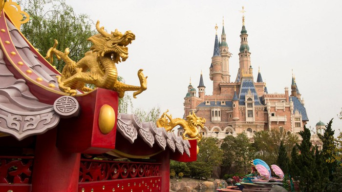 A dragon carving smiles in the foreground in front a castle at Disney Shanghai