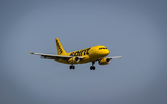 Yellow liveried plane cruising in sky.