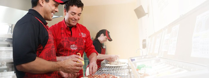 Papa John's founder John Schnatter works in the kitchen with an employee.