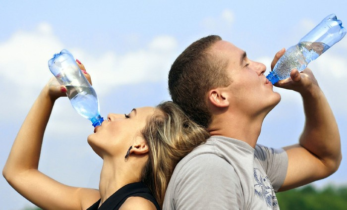 A man and a woman drink water.
