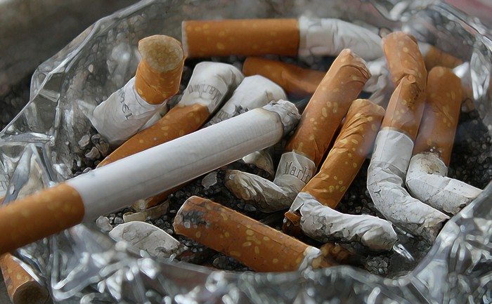 A bunch of cigarette butts in an ash tray