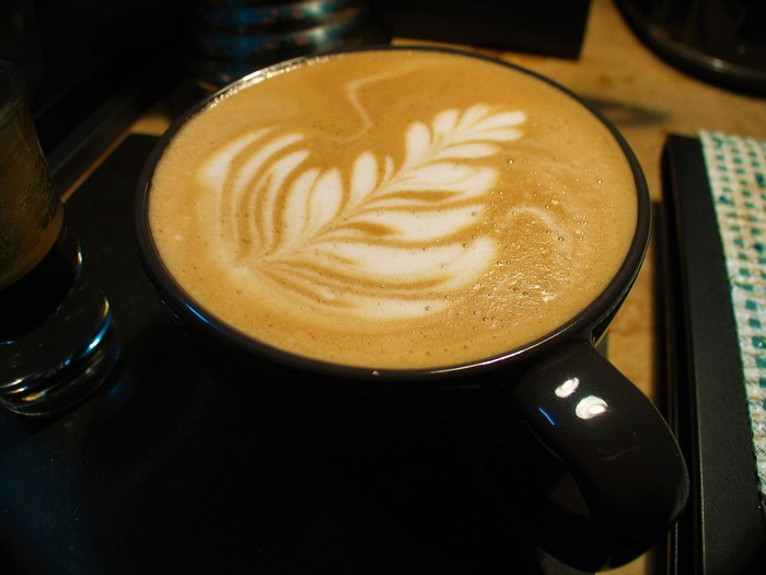 A latte with a leaf drawn in the foam