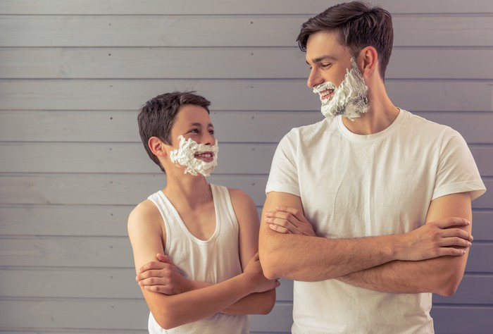 A father and son looking at each other with shaving cream on their faces.