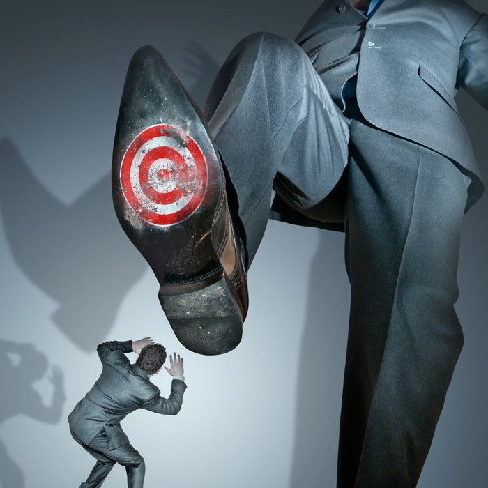 A giant businessman about to stomp on a smaller businessman -- with a target on the bottom of his shoe.