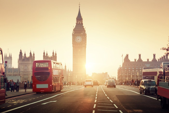 The famous Westminster Bridge with the sun setting over a double decker bus in London.