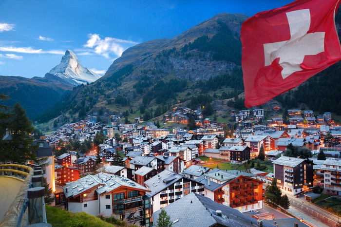 A Swiss flag hangs over houses in the town of Zermatt with the famous Matterhorn of the Swiss Alps rising in the background.