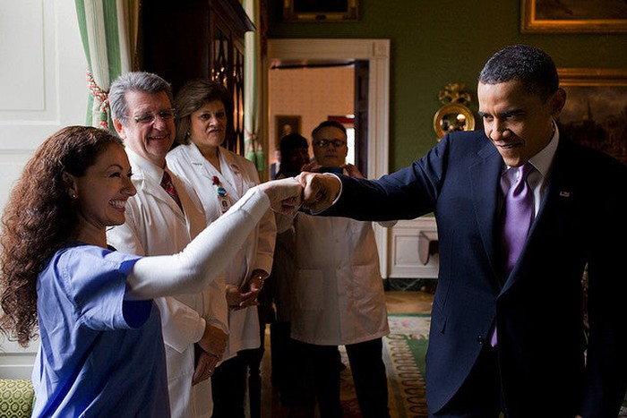 Former President Barack Obama bumping fists with a nurse in the White House and celebrating the passage of the Affordable Care Act.
