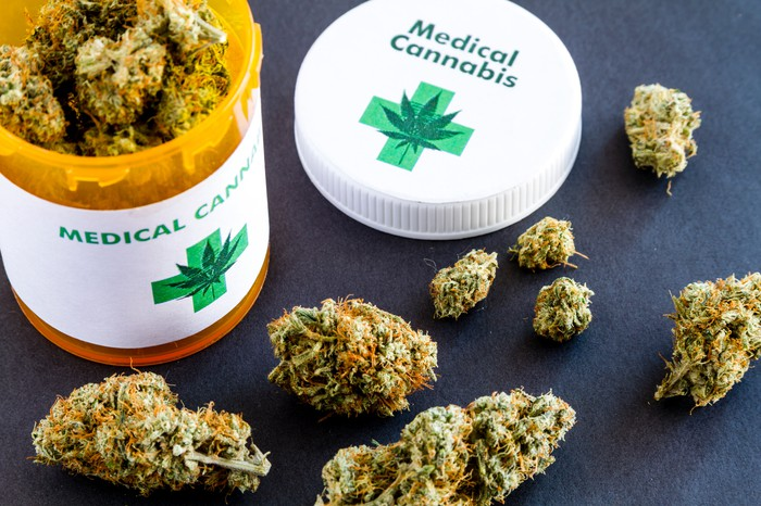 Marijuana buds sitting next to an open medical cannabis container.