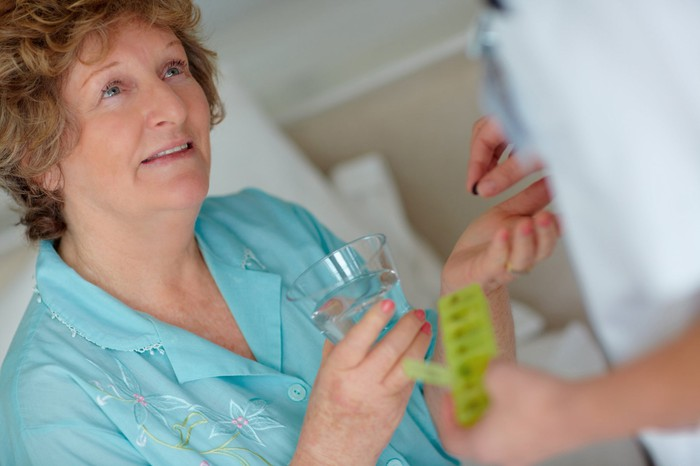 Senior woman receiving pill from doctor
