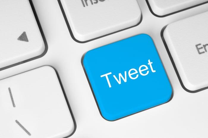 """A blue """"Tweet"""" button on a computer keyboard."""