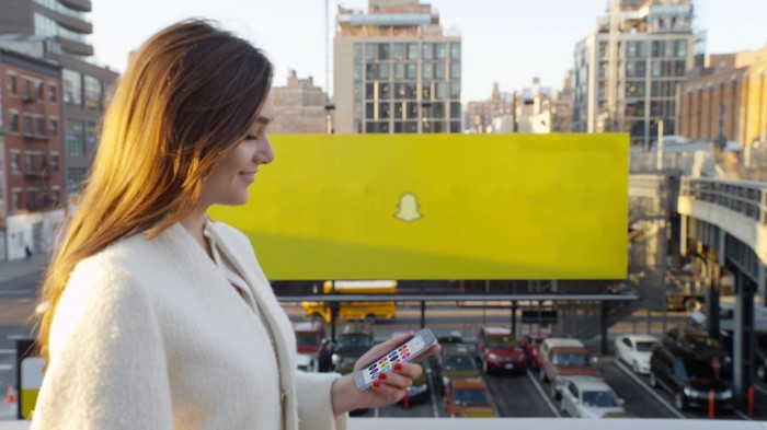 A woman using the Snapchat app in front of a large sign with the Snap logo.