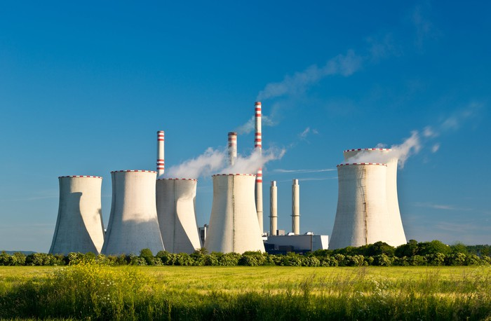 Power plant with smoke coming out of smokestacks on a sunny day.