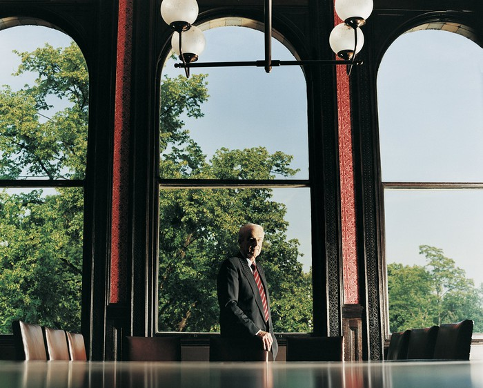 Wealthy man in a conference room by large window