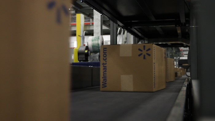 A package rolls down a shipping line at a Wal-Mart warehouse