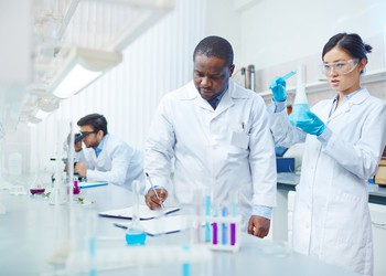 3 scientists in lab - 2 standing, 1 sitting
