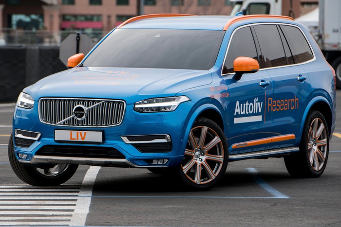 A blue Volvo SUV with Autoliv emblems on a city road.