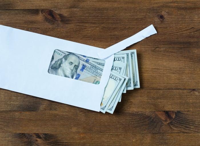 Envelope full of money on a table.