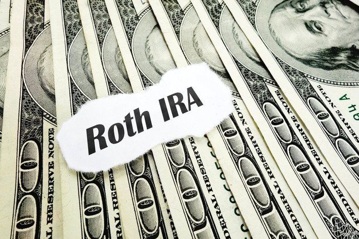 "A piece of paper with the words ""Roth IRA"" sitting atop a fanned pile of money."
