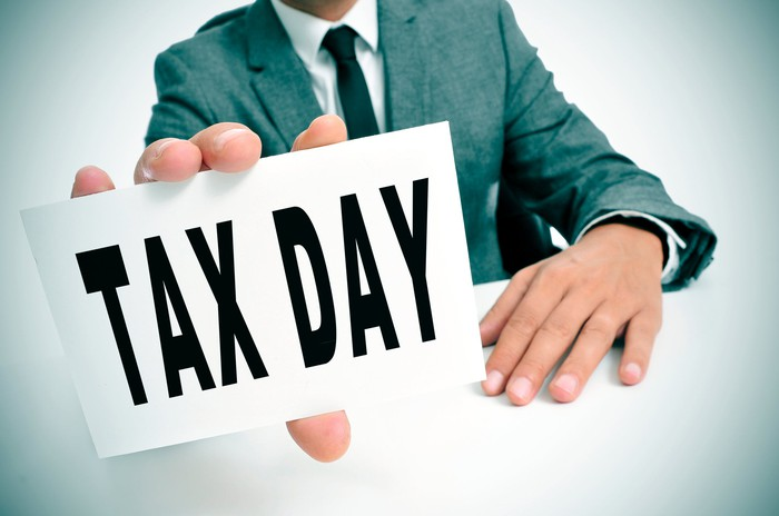"A tax professional holding a sign that says ""Tax Day"""
