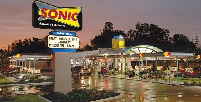 A Sonic location at night with a truck pulling up to Sonic's iconic call-box park and  order spot.
