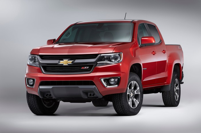 A red Chevy Colorado midsize pickup truck.