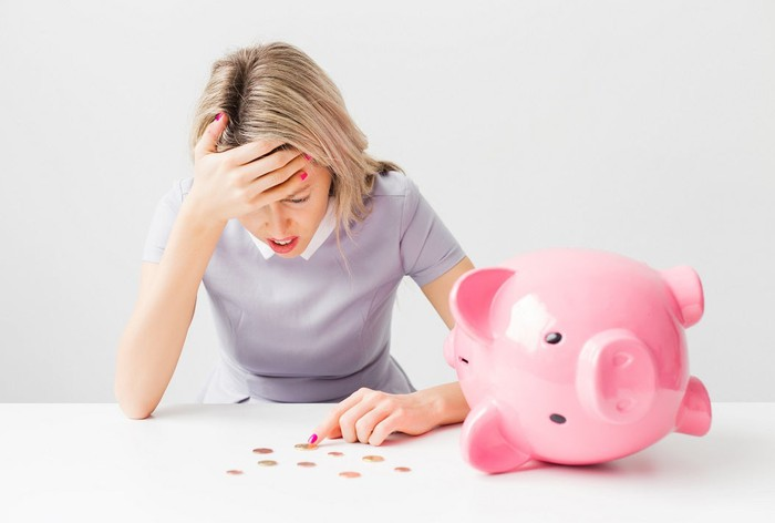 Woman confused with piggy bank nearby