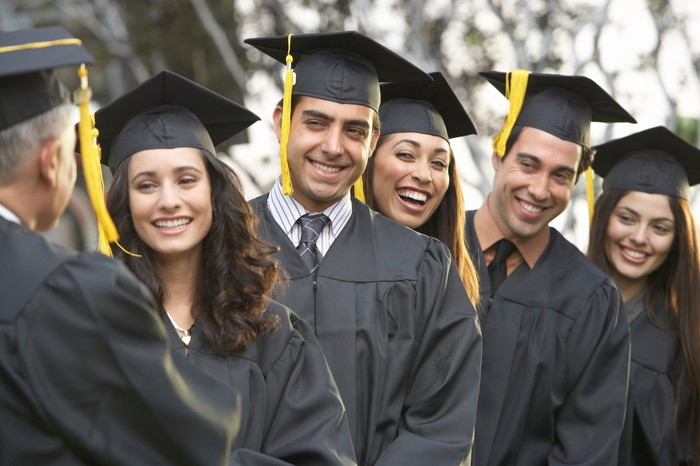 Group of college students in graduation caps and gowns.