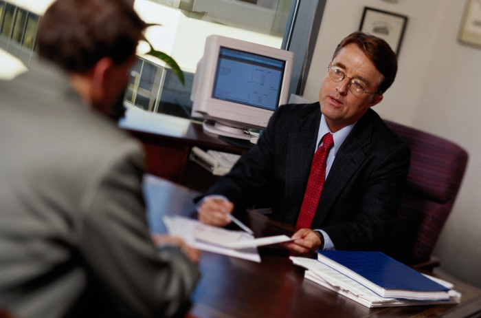 A man in a suit consulting another, at a desk.
