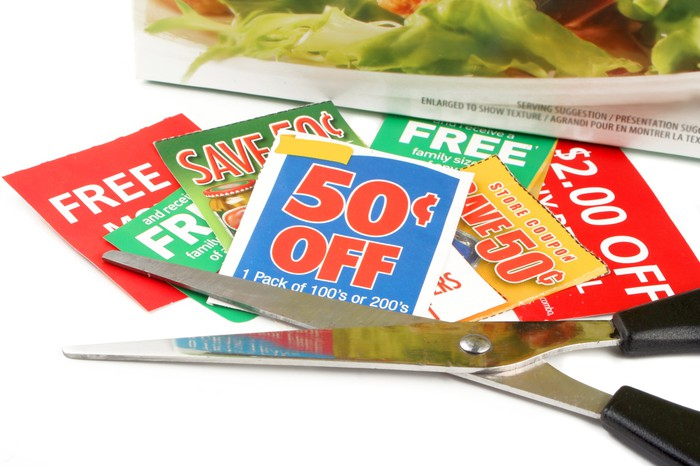 a bunch of coupons with a pair of scissors next to them