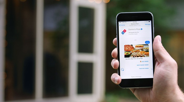 Hand holding a smartphone displaying ordering from Domino's via Facebook Messenger
