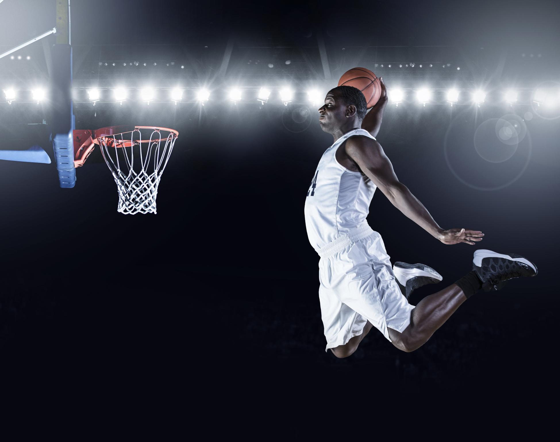 Basketball player flying through air to make a slam dunk