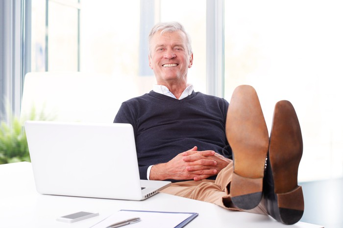 Senior investor sitting back smiling with his feet up