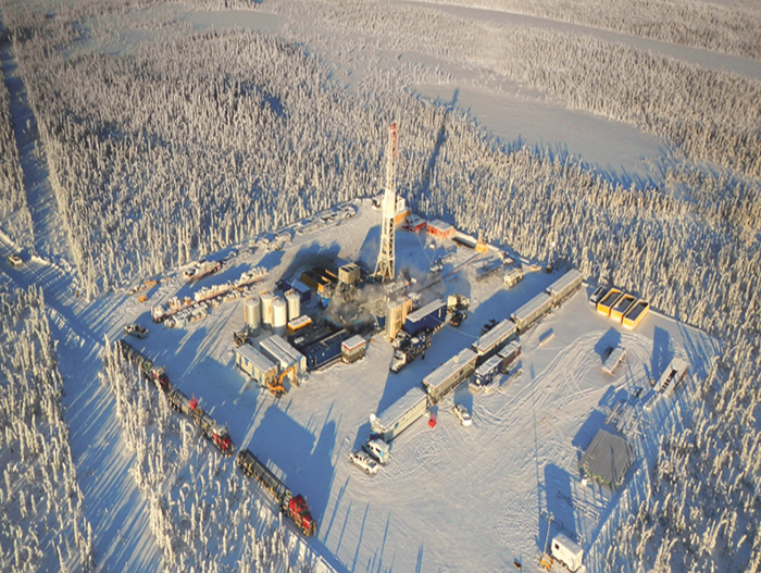 A drilling rig in the snowy Canadian landscape.