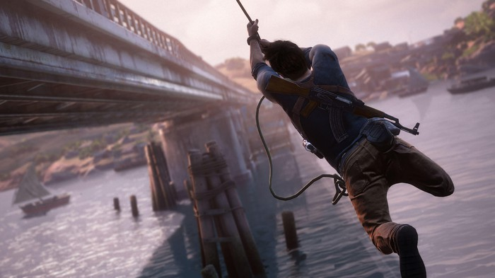 "Nathan Drake from Sony's ""Uncharted"" series swinging from a rope alongside a bridge."