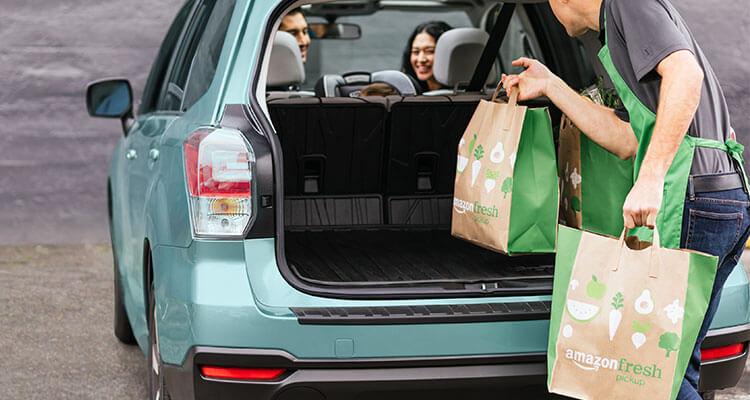 An AmazonFresh worker loads bags into a trunk.