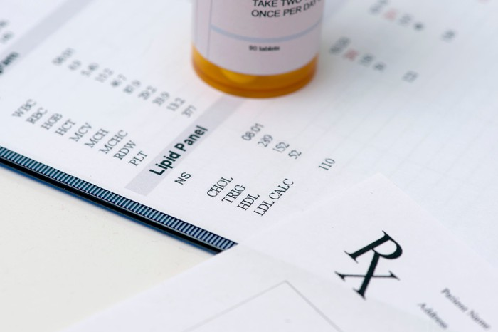 A lab report with a prescription drug bottle sitting on it.
