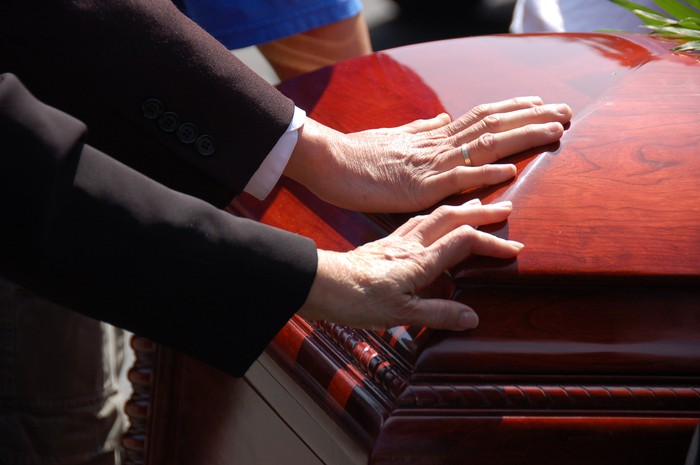 Two hands touching a closed wooden casket.