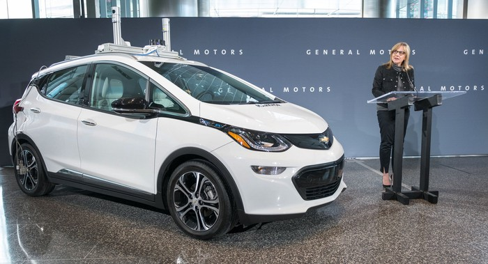 GM CEO Mary Barra stands next to a white Chevy Bolt with visible self-driving sensors.