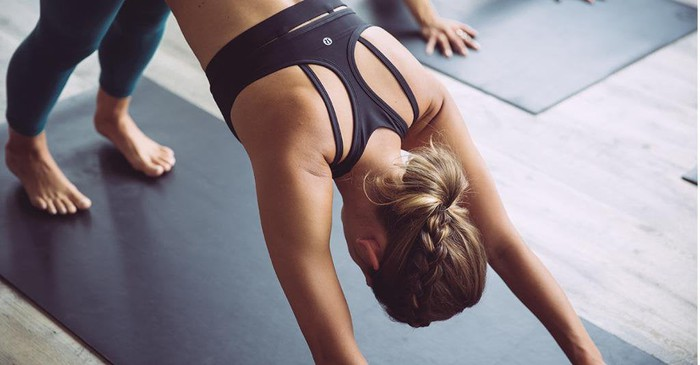 A woman doing yoga in Lululemon apparel.