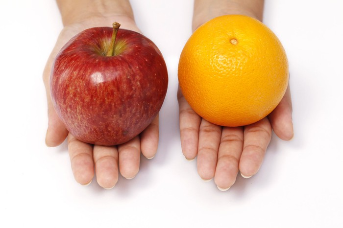 Someone holding out an apple in one hand and an orange in the other.