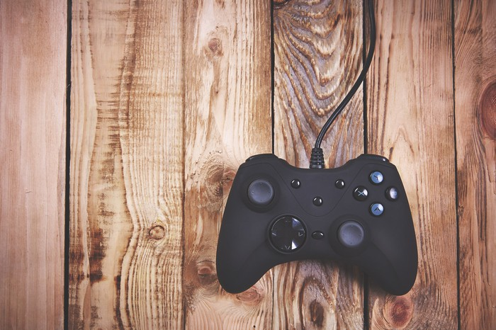 A video game controller resting on a wooden surface.