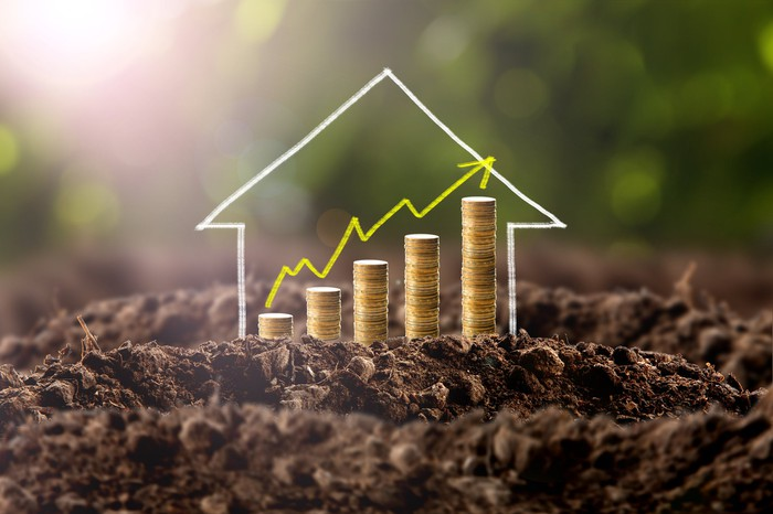Money growing in soil with a house picture.