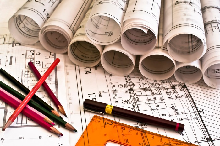 Construction plans with pencils lying on a table.