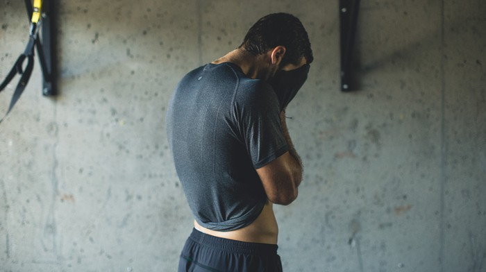 A man wipes sweat off his face with his Lululemon shirt during a workout.